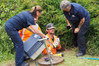 Contractor Lance Kenney emerges from the drain with the rescued kitten. With, from left, SPCA inspector Wendy Locke, contractor Ben O'Brien and SPCA inspector Adrienne Prentis. Photo / Peter de Graaf