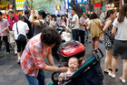 A woman feeding a baby in a market in Xian, China. Photo / Mark Mitchell