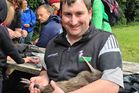 Rock Star the kiwi being cradled by Central Taranaki Young Farmers member Stephen Hicks.