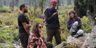 Israeli tourist Amit, only one name given, seated left, smokes a joint after a hike with friends at Malana village. Photo / AP