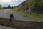 10 year old Jack Satterthwite sits on the lip of a large crack in the road in Waiau caused by the 7.8 earthquake that struck North Canterbury on November 14. Photo / File