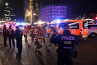 Firefighters walk past ambulances after a truck ran into a crowded Christmas market and killed several people in Berlin. Photo / AP