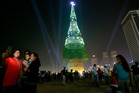 A Sri Lankan family takes photographs standing near an enormous artificial Christmas tree as others gather around it in Colombo, Sri Lanka. Photo / AP