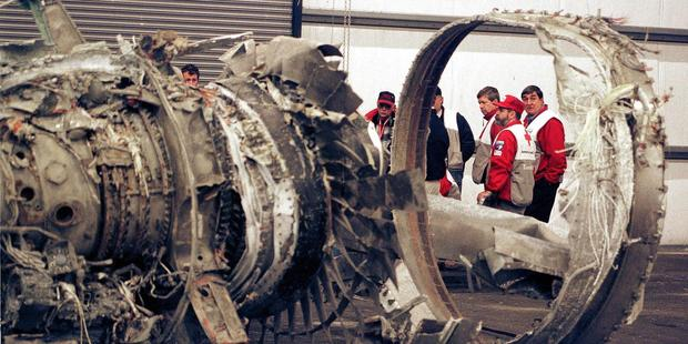 Red Cross Volunteers and family members are framed by engine wreckage from EgyptAir Flight 990. Photo / Getty Images