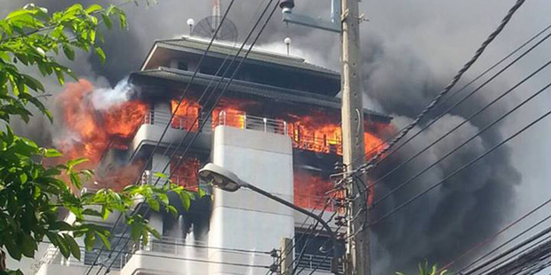 Fire crews are battling a large blaze in a Bangkok high-rise. Photo / FM91 Twitter