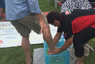 Andrew Little gets his feet washed by Shirleyanne Browne after doing a paint footprint for her at Waitangi. Photo / Claire Trevett