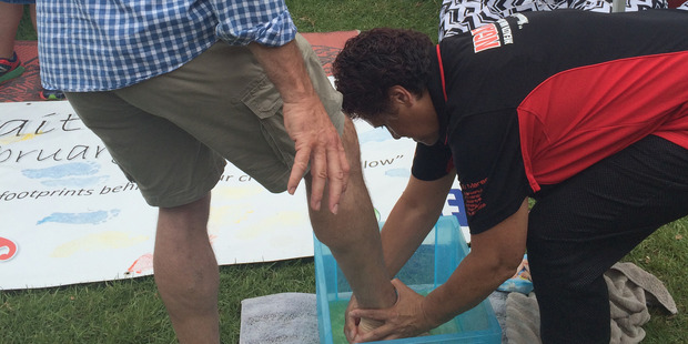 Loading Andrew Little gets his feet washed by Shirleyanne Browne after doing a paint footprint for her at Waitangi. Photo / Claire Trevett