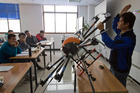 An instructor explains the operation of a drone to students at a school run by TT Aviation Technology in Beijing. Photo / AP