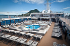 The sun-drenched sundeck featuring pool flanked by spa pools on Azamara Quest. Photo / Andrew Warner