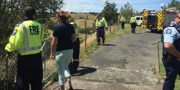 Laura Phillips of the Dannevirke SPCA (second from left) with emergency services in Dagmar St at the rescue of a sheep stuck in the mud on Tuesday.