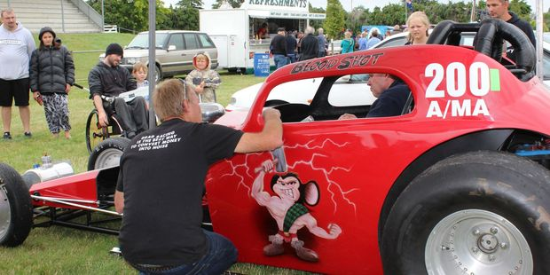 Craig Fairhurst's shirt says it all, as he checks out Blood Shot, the McHardys' dragster, with its 1948 Fiat Topolino body, an altered chassis and its own version of the Dannevirke Viking on the side.