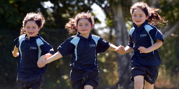 Olivia (left), Charlotte and Haylee Kelly 6, are glad to be back at Milton Primary School for their second year. Photo / Otago Daily Times
