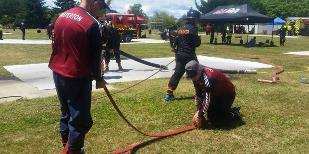Prize-winning Carterton firefighters Mike Hicks and Steve Fennell asemble the hose at the Waterway Competition at Turangi. PHOTO/FACEBOOK