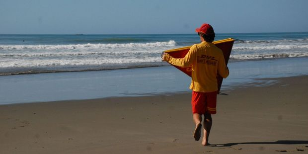 A lifeguard sets up the flags ahead of another day at the beach.