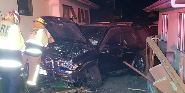 A vehicle came to a stop in a driveway between two homes facing the road.