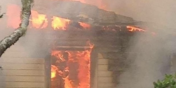 Massive flames can be seen engulfing the property. Photo / Devon Venter
