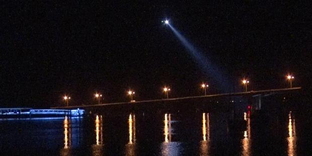 The Westpac helicopter used its spotlight to search the harbour. Photo / Daniel Hines