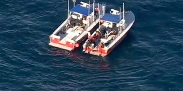 In this still frame from video provided by KABC-TV, divers aboard two rescue boats search for wreckage. Photo / AP