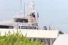 NZ Police launch departs Beach Haven wharf after recovering a body.