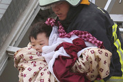 A child is rescued from a toppled building after a 6.4-magnitude earthquake in Tainan, Taiwan. Photo / AP