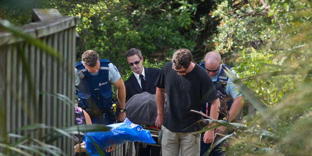 Officers with the body of the young man who drowned. Photo / Stephen Parker