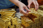 An employee arranges one kilogram gold bars for a photograph at the YLG Bullion International Co. headquarters in Bangkok, Thailand. Photo / Bloomberg