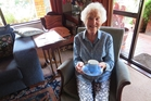 Janet Nairn holding a cup and saucer that was only slightly cracked after being buried under bricks from a chimney that collapsed in the 1931 earthquake. Photo / Nicki Harper
