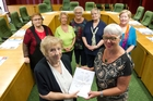 Rosemary Michie (front left) and mayor Steve Chadwick (front right) holding the petition with other meeting members present. Photo / Stephen Parker