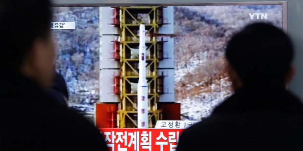People watch a TV news reporting a rocket launch in North Korea, at Seoul Railway Station in Seoul. Photo / AP
