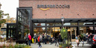 Customers wait in line to enter the Amazon Books store in Seattle. More e-tailers are now choosing to open physical stores. Bloomberg photo by David Ryder.