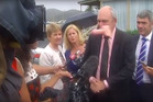 Government minister Steven Joyce is hit in the face by a pink dildo thrown at him as he talks to media in Waitangi. Photo/NEWSHUB