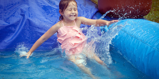 Kahurangi Moore, 5, slides down the blow-up waterslide at the Greerton Family Festival on Saturday. Photo/Andrew Warner