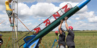 Jack Davies (obscured) gets help during preparations to launch his rocket in Huntly yesterday. Photo / Alan Gibson