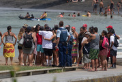 A crowd gathers on a jetty at the edge of Raglan Harbour after the teen died after jumping from the bridge. Photo / Alan Gibson