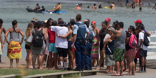 Loading A crowd gathers on a jetty at the edge of Raglan Harbour after the teen died after jumping from the bridge. Photo / Alan Gibson