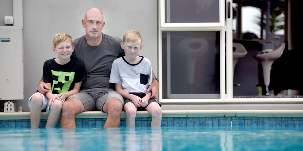 Rob Clark, pictured with sons Elliot, 9, and Cameron, 11, is upset new pool fencing regulations could set him back thousands of dollars. Photo / George Novak