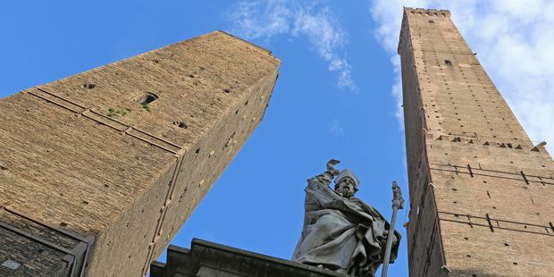 Torre Asinelli and Torre Garisenda towers and statue of St Petronio tower over Bologna. Photo / 123Rf