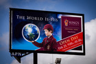 The billboard shows a boy in King's uniform holding the world in the palm of his hand.