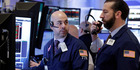 Traders Fred DeMarco, left, and Greg Mulligan confer on the floor of the New York Stock Exchange. File photo / AP