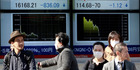 Pedestrians stand in front of an electronic stock board showing Japan's Nikkei 225, left, at a securities firm in Tokyo. Asian markets tumbled yesterday.