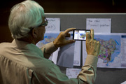 A man takes pictures of planned zoning changes at a public meeting in Kohimarama earlier this week. Photo / NZ Herald
