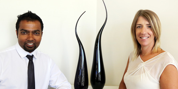 STUNNING GIFT: Property Brokers' Ritesh Verma accepts two glass artworks from Whanganui glass artist Katie Brown. PHOTO/STUART MUNRO