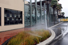 Despite the wet morning, sprinklers were in action outside Hawke's Bay Opera House, Hastings, yesterday. Photo / Paul Taylor