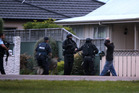 The armed offenders squad apprehends a man believed to have been carrying a gun on city streets. Photo / Duncan Brown