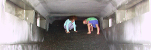 Local children are pictured playing in a blocked stormwater outfall beneath Napier's viewing platform in January, since secured by a steel gate.