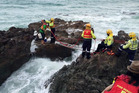 Waipu firefighters prepare to help two people stranded on rocks while fishing to walk across a ladder at the northern end of Langs' Beach.
