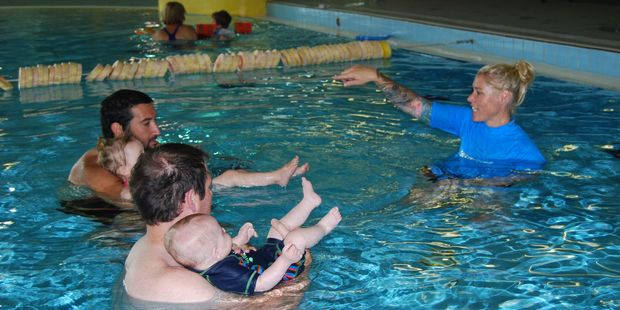 Charli with dad Matt Johnson, left, and Jacob with dad Garry Dillon practise moving in water with Swim Magic co-ordinator Hollee Wilton. PHOTO/ALISA YONG