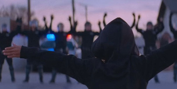 A hooded figure runs towards a line of police officers, who put their arms up. Photo / Beyonce / YouTube