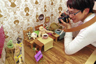 Kimiko Suzuki, who operates Yawarakan's café in Tokyo, takes photos of stuffed animals who are spending time there. Photo / Japan News