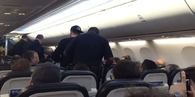 The man, seen wearing a backward baseball cap, was escorted off the plane by law enforcement. Photo / Twitter, mamashepesq